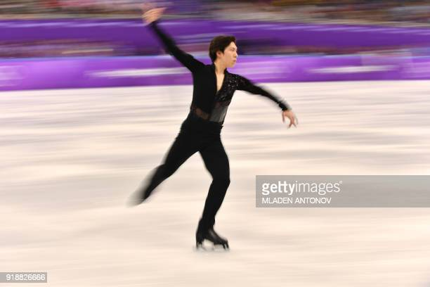 This slow shutter speed exposure shows Japan's Keiji Tanaka warming up before competing in the men's single skating short program of the figure...