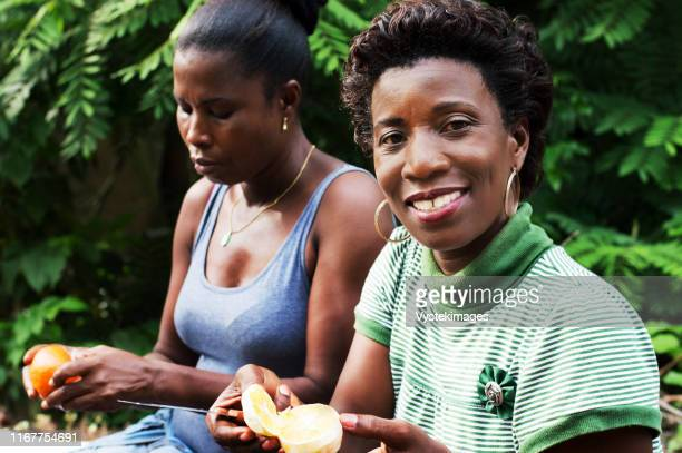 this smiling young woman is cutting an orange. - côte d'ivoire stock pictures, royalty-free photos & images