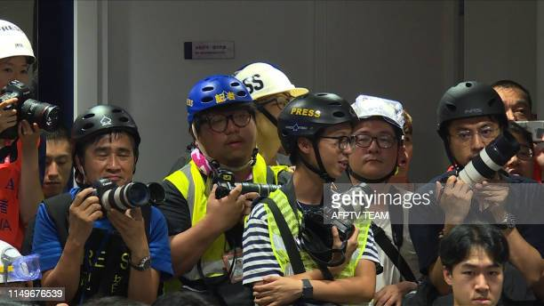 This still image taken from an AFPTV video shows Hong Kong journalists dressed in high visibility jackets and helmets during a police press...