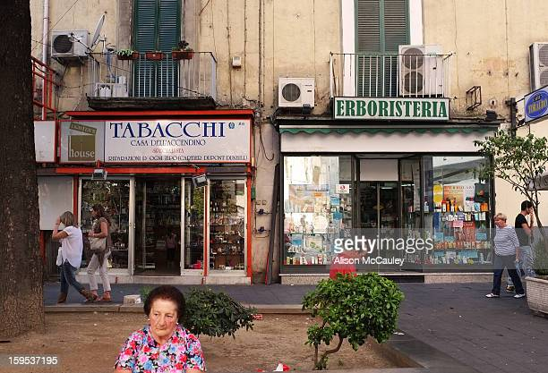 This street scene shows the rhythm of life in the lively and disheveled streets of Naples. People rest and walk past the old-fashioned shops. The...