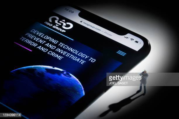 This studio photographic illustration shows a smartphone with the website of Israel's NSO Group which features 'Pegasus' spyware, on display in Paris...