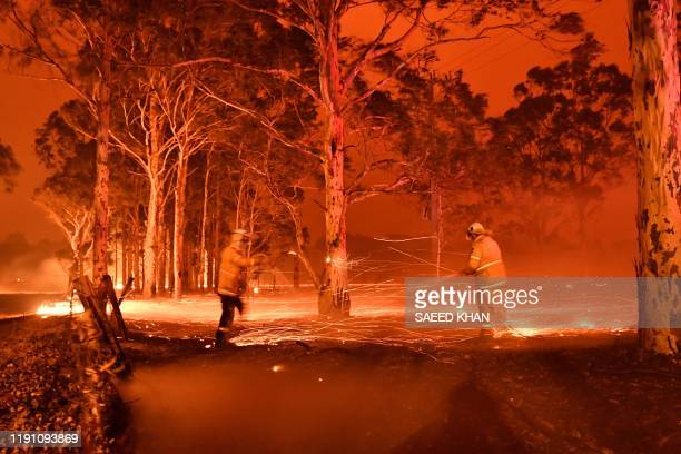 This timedexposure image shows firefighters hosing down trees as they battle against bushfires around the town of Nowra in the Australian state of...
