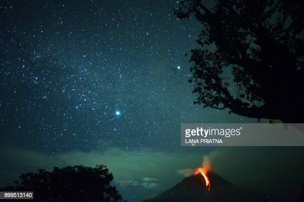 TOPSHOT This timedexposure photo taken on December 28 2017 shows Mount Sinabung volcano spewing lava that lights up the night sky in Karo North...