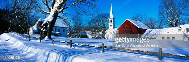 This town was settled in 1776 It is a typical image of New England in the winter There is a white church with tall steeple snow covered trees a...