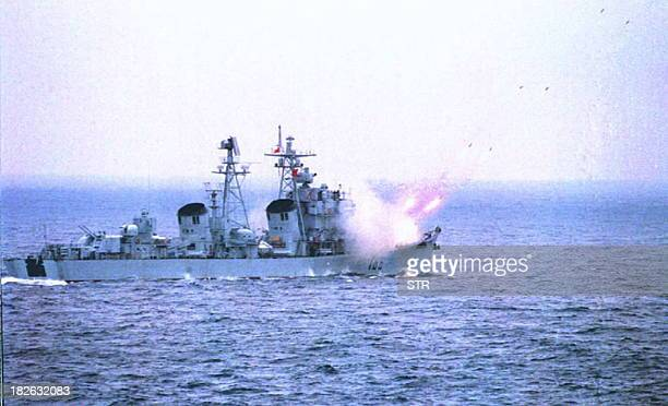 This undated file photo released 20 March by the official Chinese news agency Xinhua shows a Chinese destroyer firing missiles at a submarine from...