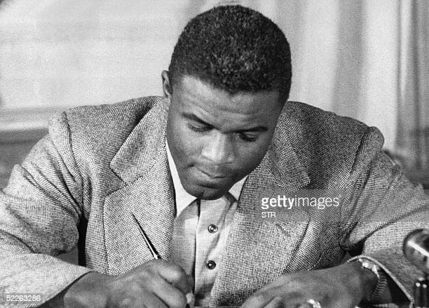 This undated file photo shows US baseball star Jackie Robinson as he signs a then-record contract to play for the Brooklyn Dodgers in New York....