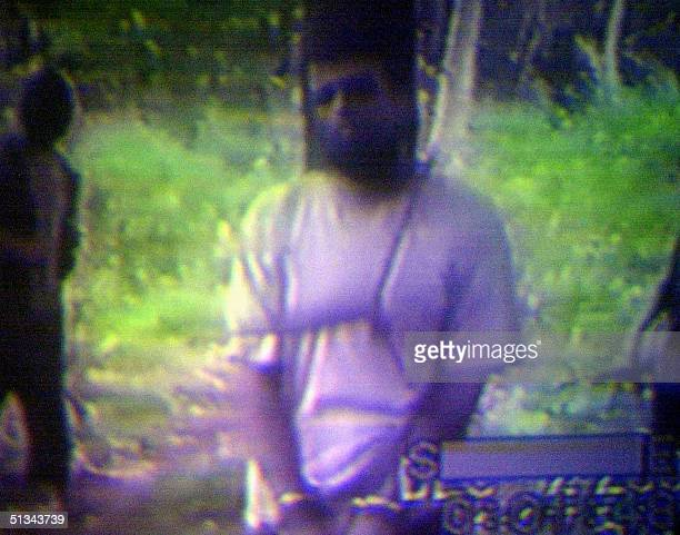 This undated grab from a videotape recovered 28 December 2000 shows a restrained American captive Jeffrey Schilling being guarded by Abu Sayyaf...