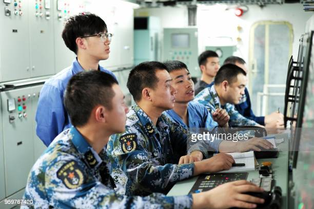 This undated photo released on May 18 2018 shows People's Liberation Army sailors working on board China's first domestically manufactured aircraft...