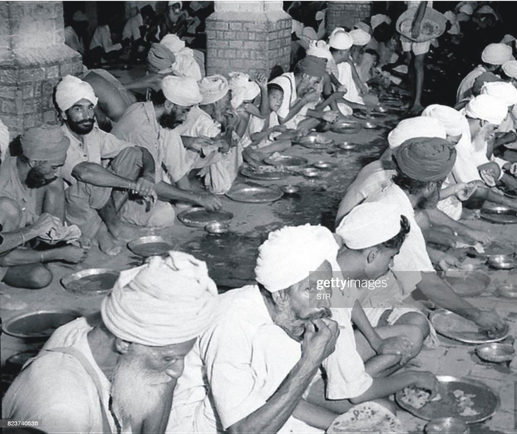 This undated photo taken circa 1947/1948 shows Sikh people eating free food at a relief camp at Khalsa college in Amritsar following unrest in the...
