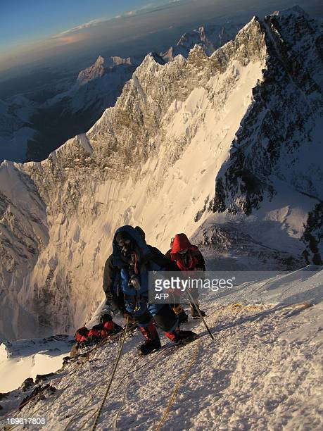 This undated photograph shows unidentified mountaineers as they walk past the Hillary Step whilst pushing for the summit of Mount Everest as they...