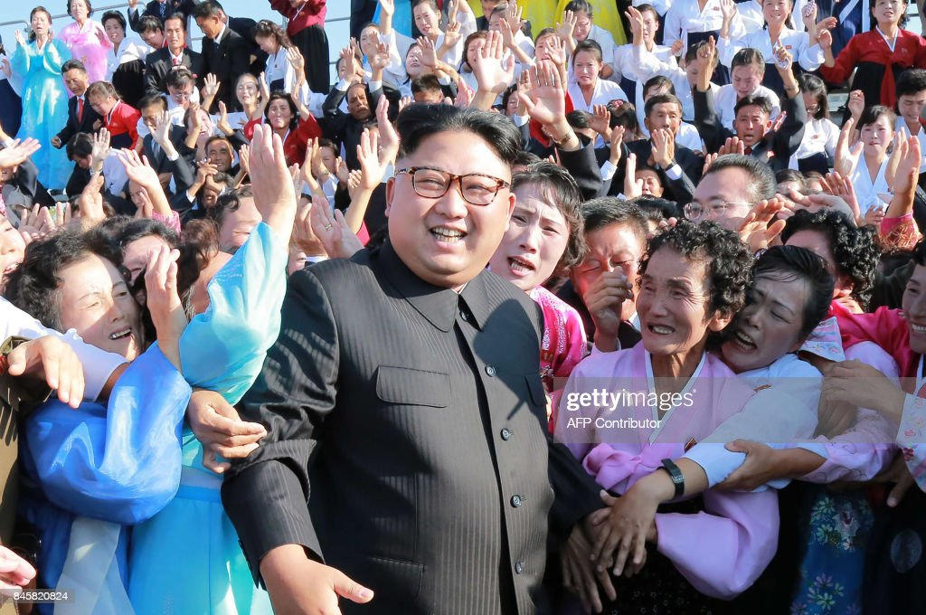 This undated picture released from North Korea's official Korean Central News Agency (KCNA) on September 12, 2017 shows North Korean leader Kim Jong-Un (C) attending a photo session with teachers who volunteered to work at branch schools on islands and schools in forefront line and mountainous areas, in Pyongyang. / AFP PHOTO / KCNA VIA KNS / STR / South Korea OUT / REPUBLIC OF KOREA OUT ---EDITORS NOTE--- RESTRICTED TO EDITORIAL USE - MANDATORY CREDIT 'AFP PHOTO/KCNA VIA KNS' - NO