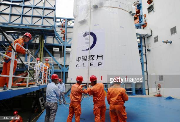 This undated picture released on May 21 2018 shows employees loading the Queqiao satellite at the Xichang launch centre in Xichang China's...