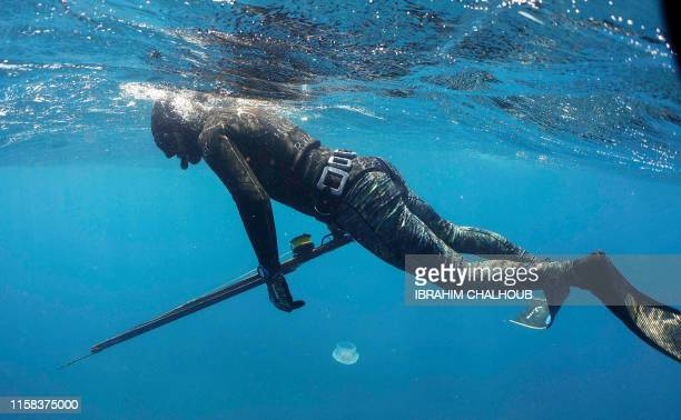 This underwater picture taken on July 29 shows a spearfishing practitioner swimming past a jelly fish off the coast of the northern Lebanese town of...