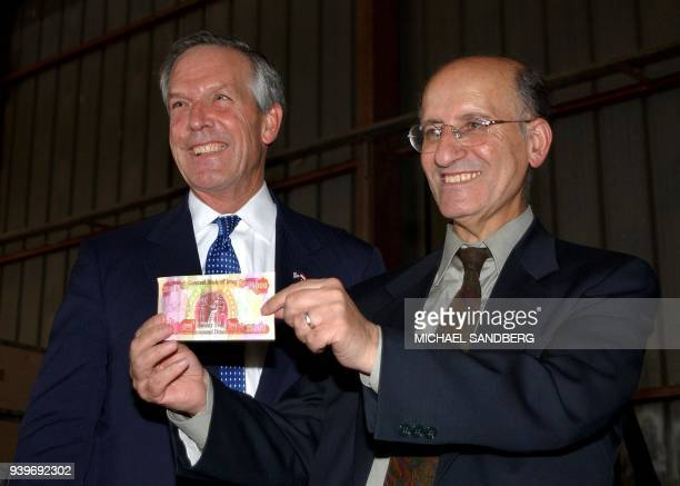 This US Navy handout photo shows Iraq's Central Bank Governor Sinan alShibibi displaying a new Iraqi diner with US Secretary of Commerce Don Evans...