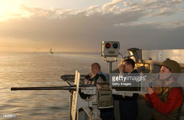 This U.S. Navy handout photo shows sailors manning a .50-caliber machine gun on February 26, 2003 at sea onboard the USS Kitty Hawk in the Strait of...