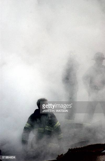 This US Navy photo released 17 September shows a firefighter emerging from the smoke and debris of the World Trade Center 14 September 2001 The twin...