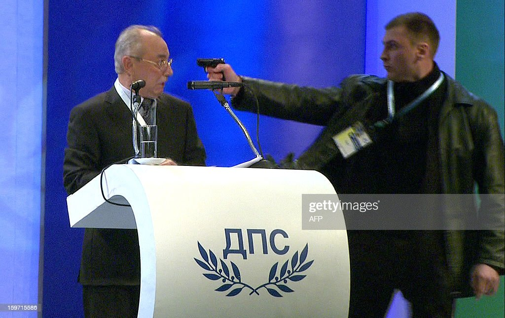 This video grab broadcast by Bulgarian television channel BTV shows a man (R) pointing a pistol at leader of the Turkish minority Movement for Rights and Freedoms (MRF) party Ahmed Dogan during his speech at a national party conference in Sofia on January 19, 2013. Dogan was addressing the delegates at the conference when the man rushed up to the podium and put a pistol to his head. The attacker however failed to produce a shot and was quickly disarmed by the delegates, witnesses told state BNR radio. RESTRICTED TO EDITORIAL USE - MANDATORY CREDIT 'AFP PHOTO /BTV' - NO