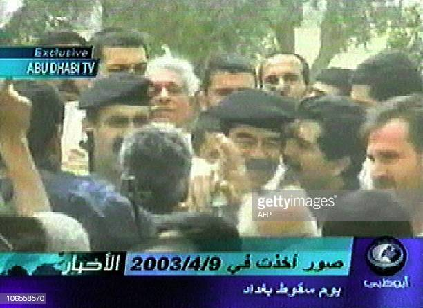 This video grab from Abu Dhabi TV shows footage broadcast 18 April 2003 of toppled Iraqi leader Saddam Hussein embraced by his son Qusay during a...