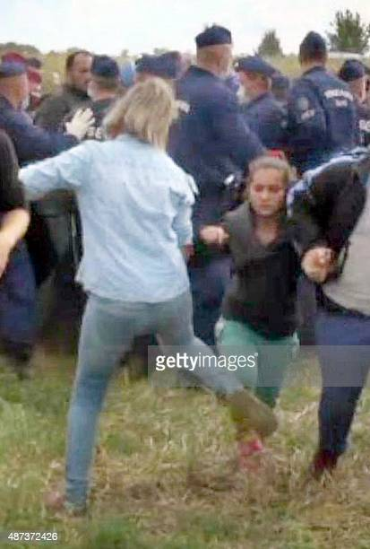 This video grab made on September 9 2015 shows a Hungarian TV camerawoman kicking a child as she run with other migrants from a police line during...