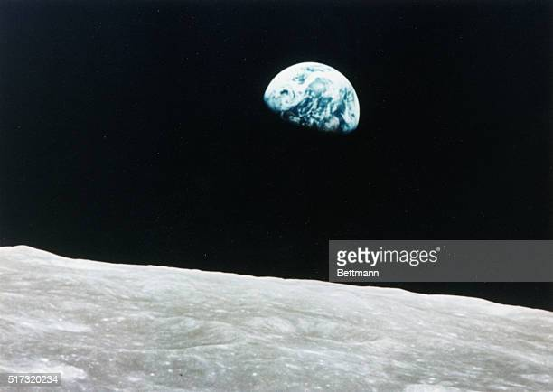 This view of the rising earth greeted astronauts Borman Anders and Lovell as they came from behind the moon after the lunar orbit insertion burn...