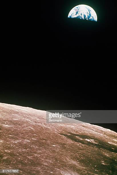 This view of the rising Earth greeted the Apollo 8 astronauts as they came from behind the moon after the lunar orbit insertion burn Earth is about...