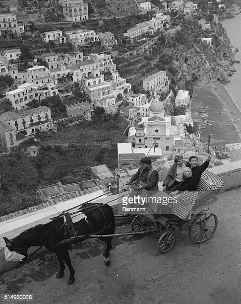 This view shows how Positano lies along the small beach and against the jagged rocks Riding in a colorful horsedrawn carriage writer Reynolds Packard...