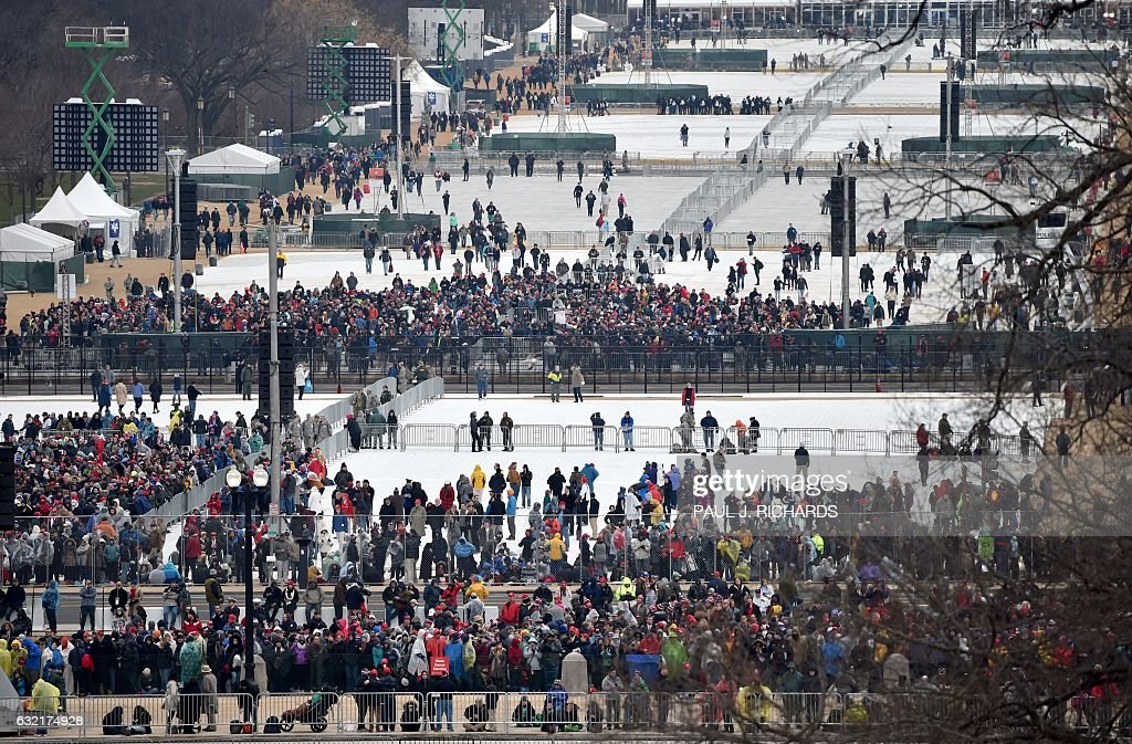 TOPSHOT - This view taken January 20, 2017 shows people gathering on the mall to witness President-elect Donald Trump take the oath of office as the 45th president of the United States. / AFP / Paul J. Richards