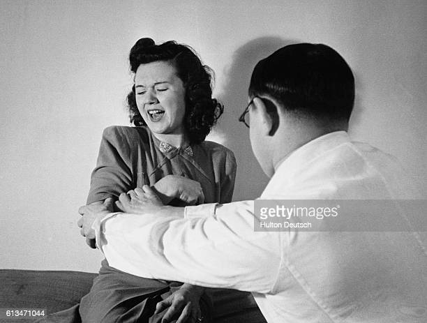 This woman has been hypnotised and told that her arm and hand are paralysed and will remain so until the doctor blows his nose When he tries to pull...