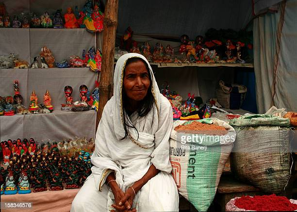 This woman sells handmade and handpainted toys at the market Her white sari indicates she is a widow since widows are not allowed to wear color in...