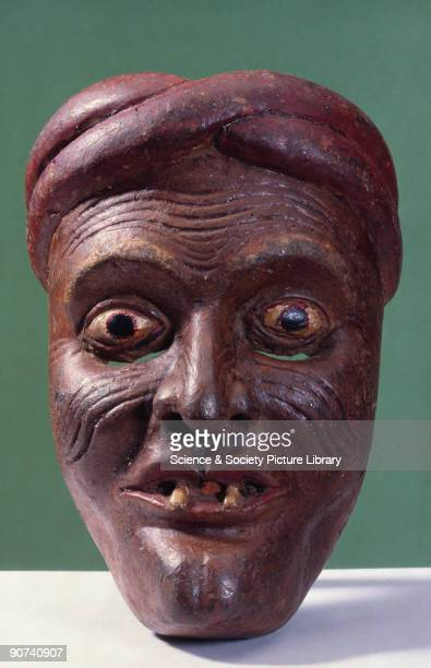 This wooden mask shows a brownfaced gaptoothed wrinkled man wearing a turban possibly a peasant from the kolam masked play and was worn for healing...