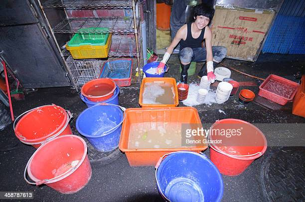 This young boy is washing dishes at the back of a restaurant, in Gongguan in Taipei. While everyone behing him is chatting and having fun, he's at...