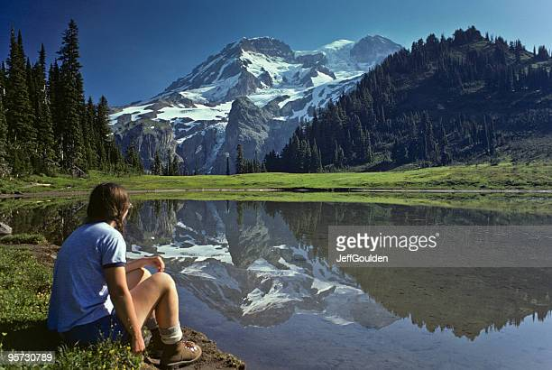 young female hiker at aurora lake with mt rainier reflection - mt rainier stock pictures, royalty-free photos & images
