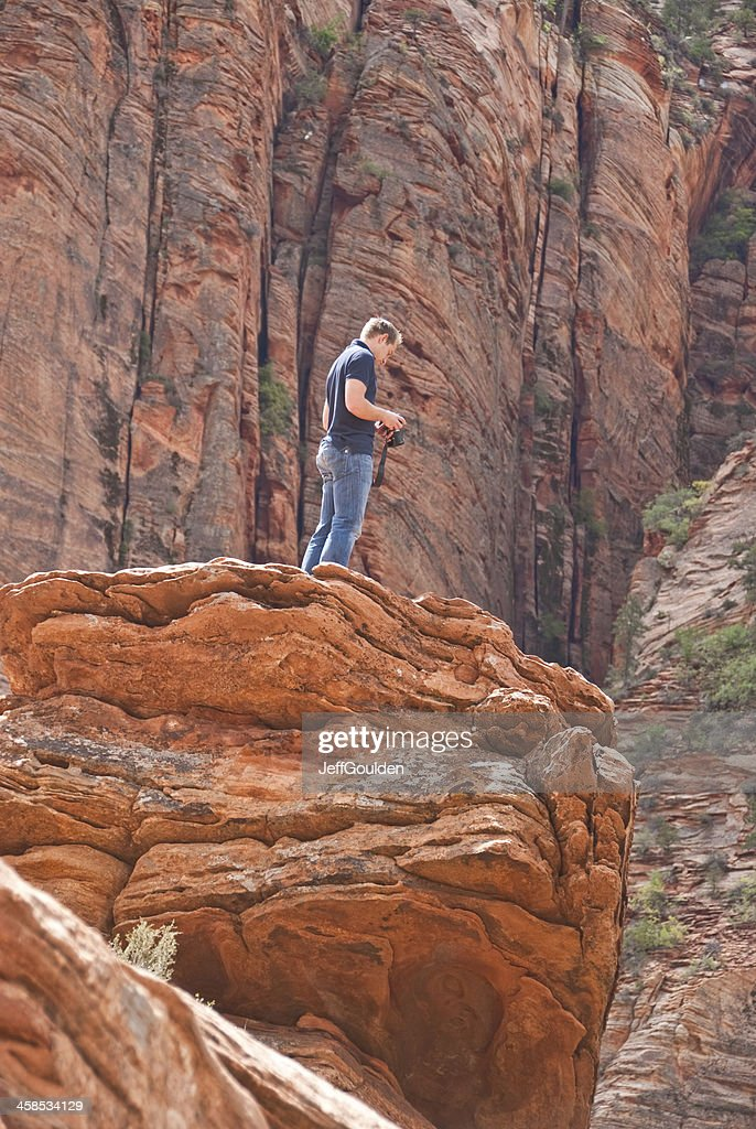 Young Man Taking Picture from a Rock Formation : Stock Photo