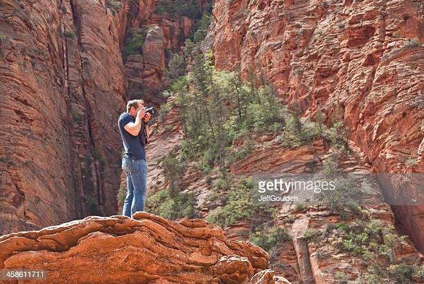 Young Man Taking Picture from a Rock Formation