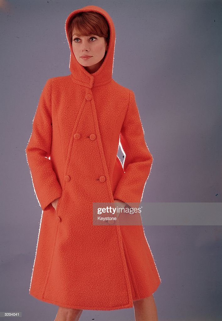 This young lady models the latest French fashions. This bright orange coat is just the thing for those dark, cold winter nights.