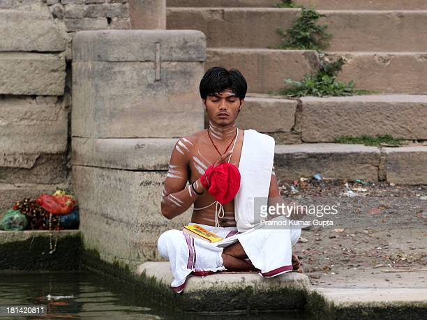 This young man is chanting some mantra with the help of beads which are covered with red cloth. Picture was shot in Varanasi, India on 17 March 2013,...