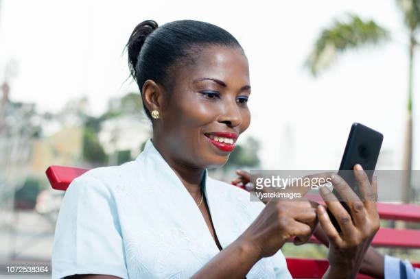 this young woman consults her phone with  smile on her face. - femme ivoirienne photos et images de collection