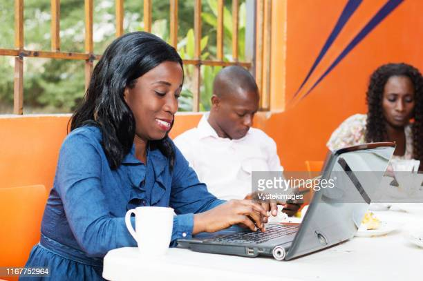 this young woman sitting at the restaurant working on a laptop. - côte d'ivoire stock pictures, royalty-free photos & images