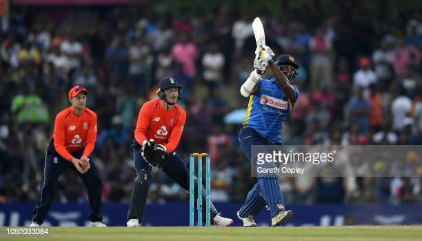 Thisara Perera of Sri Lanka hits out for six runs watched England wicketkeeper Jos Buttler and Joe Root during the 2nd One Day International match...