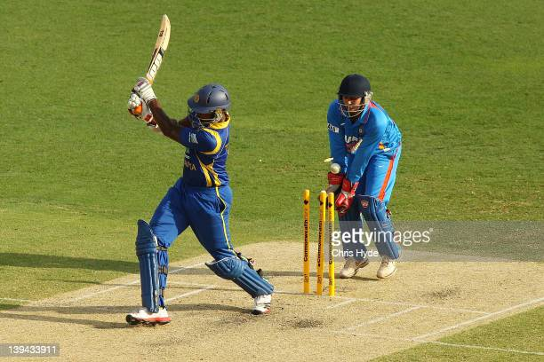 Thisara Perera of Sri Lanka is bowled out by Suresh Raina of India during game eight of the One Day International Series between India and Sri Lanka...