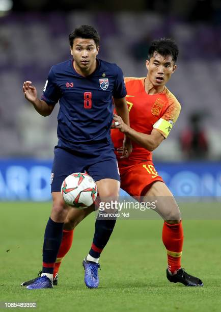 Thitiphan Puangjan of Thailand tackles with Zheng Zhi of China during the AFC Asian Cup round of 16 match between Thailand and China at Hazza Bin...