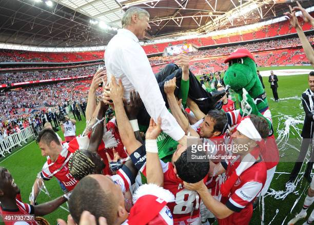 Thje Arsenal squad throw manager Arsene Wenger in the air after the FA Cup Final between Arsenal and Hull City at Wembley Stadium on May 17 2014 in...