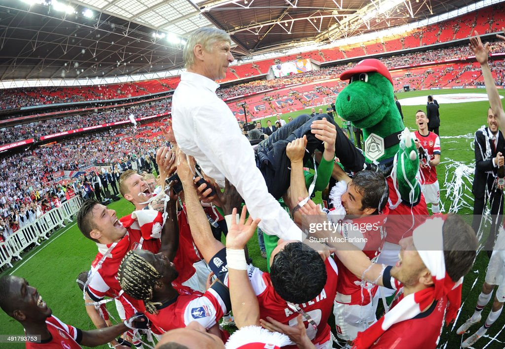 Thje Arsenal squad throw manager Arsene Wenger in the air after the FA Cup Final between Arsenal and Hull City at Wembley Stadium on May 17, 2014 in London, England.