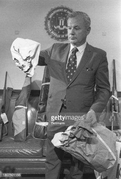 Thmas Nally, FBI assistant Special Agent in charge of the Detroit office, shows newsmen the weapons and Klan material found when agents searched the...