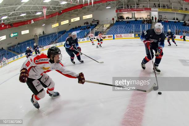 Théo Campagna of the Switzerland Nationals battles for the puck in the second period with Jake Sanderson of the US Nationals during day2 of game two...