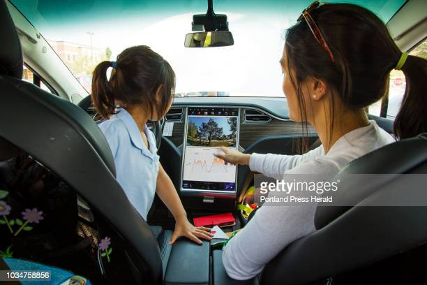 Tho Ngo of Windham shows her daughter Elsa something on the center console computer display inside the elder Ngos 2016 Tesla Model X during an...