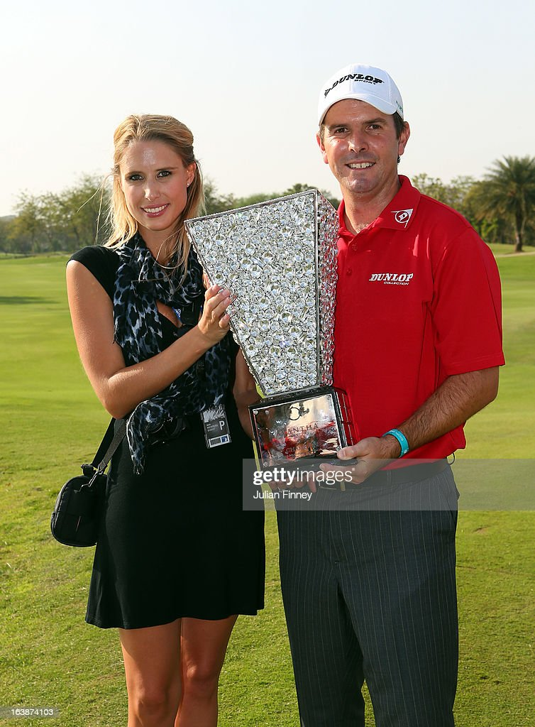 Thomas Aiken of South Africa with his wife Kate Aiken pose with the winners trophy during day four of the Avantha Masters at Jaypee Greens Golf Club on March 17, 2013 in Delhi, India.