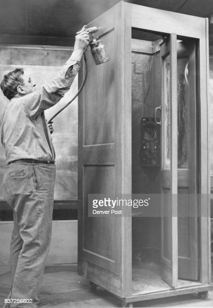 Thomas Alford sprays a refinished telephone booth Credit Denver Post