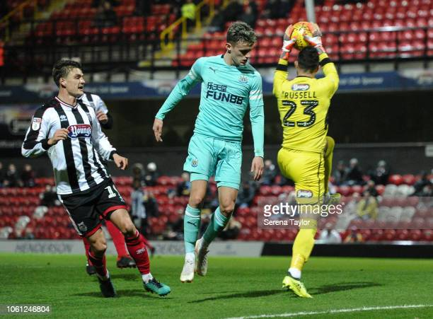 Thomas Allan of Newcastle United challenges Grimsby Town FC Goalkeeper Sam Russell during the Checkatrade Trophy Match between Grimsby Town FC and...