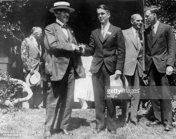 Thomas Alva Edison , Henry Ford and Charles Lindbergh congratulate the young scientist Wilbur Huston , who wins a price. Photograph. August 14th...